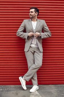 Jovem homem brutal bonito em um terno de moda perto do portão vermelho