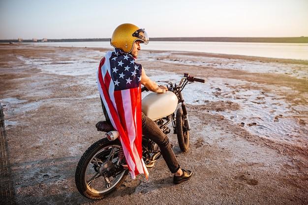Jovem homem brutal com capacete dourado e capa da bandeira americana sentado em sua motocicleta olhando para longe