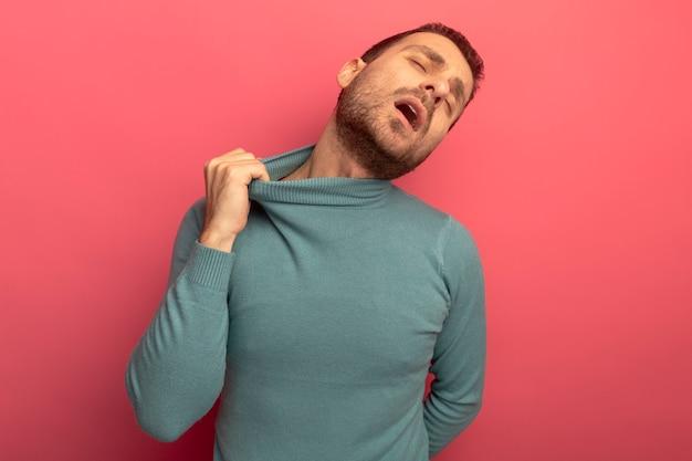 Jovem homem cansado, caucasiano, puxando a gola do suéter de gola alta com os olhos fechados, mantendo a mão atrás das costas isolada no fundo carmesim com espaço de cópia