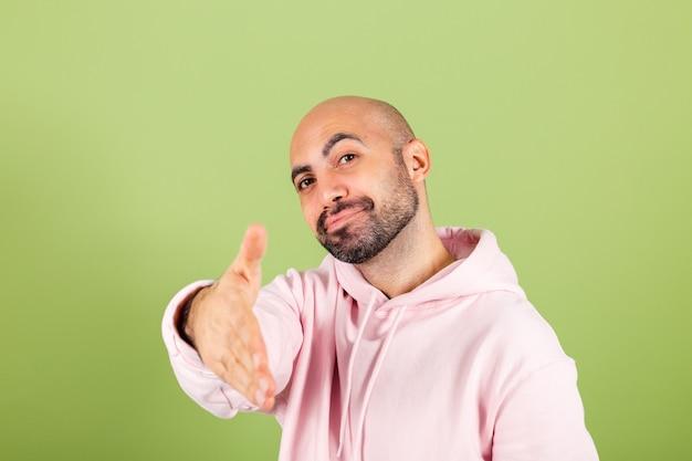 Jovem homem careca caucasiano com capuz rosa isolado, amigável, oferecendo um aperto de mão como saudação e boas-vindas