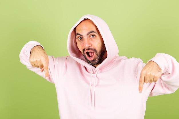 Jovem homem careca, caucasiano, com capuz rosa isolado, positivo chocado surpreso e animado apontando o dedo para baixo