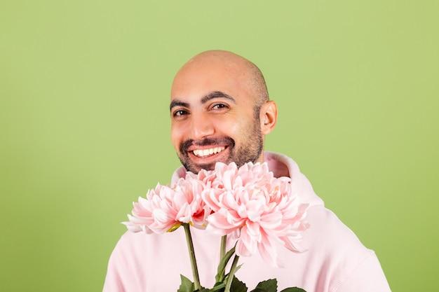Jovem homem careca, caucasiano, com capuz rosa isolado, segurando um buquê de flores feliz sorrindo
