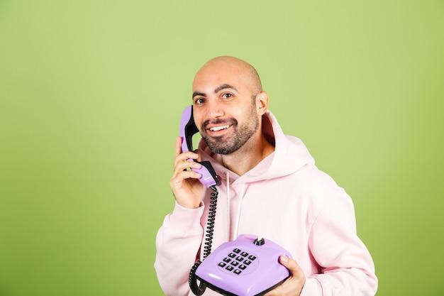 Jovem homem careca, caucasiano, com capuz rosa isolado, segurando um telefone fixo com um rosto feliz e surpreso Foto Premium
