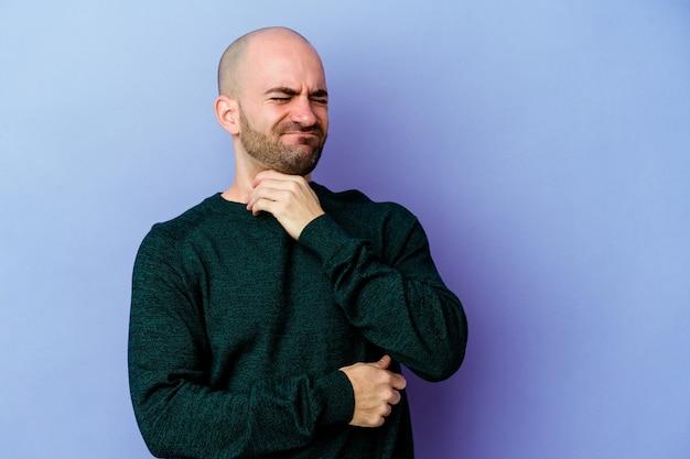 Jovem homem careca caucasiano em roxo sofre de dor na garganta devido a um vírus ou infecção.