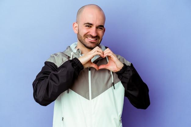Jovem homem careca caucasiano isolado em um fundo roxo, sorrindo e mostrando uma forma de coração com as mãos.