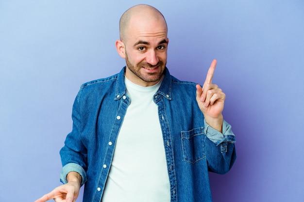 Jovem homem careca, caucasiano, isolado na parede roxa apontando para diferentes espaços de cópia, escolhendo um deles, aparecendo com o dedo