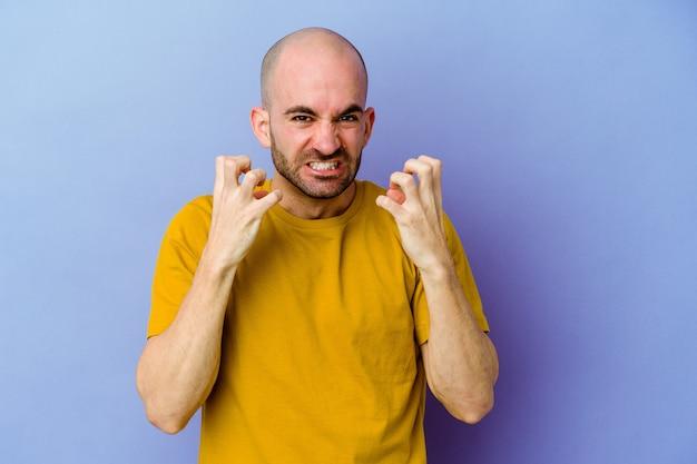 Jovem homem careca, caucasiano, isolado na parede roxa, gritando e gritando com as mãos tensas