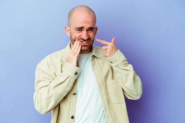 Jovem homem careca caucasiano isolado na parede roxa, tendo uma forte dor nos dentes, dor molar.