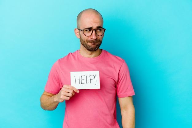 Jovem homem careca, caucasiano, segurando um cartaz de ajuda isolado em roxo confuso, sente-se em dúvida e inseguro.