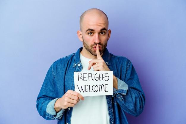 Jovem homem careca, caucasiano, segurando um cartaz de boas-vindas aos refugiados, isolado no fundo azul, mantendo um segredo ou pedindo silêncio.