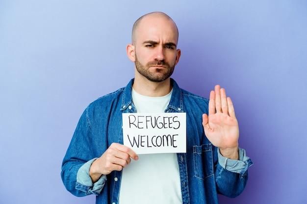 Jovem homem careca caucasiano segurando um cartaz de boas-vindas de refugiados isolado na parede azul em pé com a mão estendida, mostrando o sinal de pare, impedindo-o.