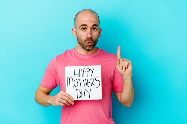 Jovem homem careca caucasiano segurando um cartaz de dia das mães feliz isolado na parede azul, tendo uma ótima ideia, o conceito de criatividade.