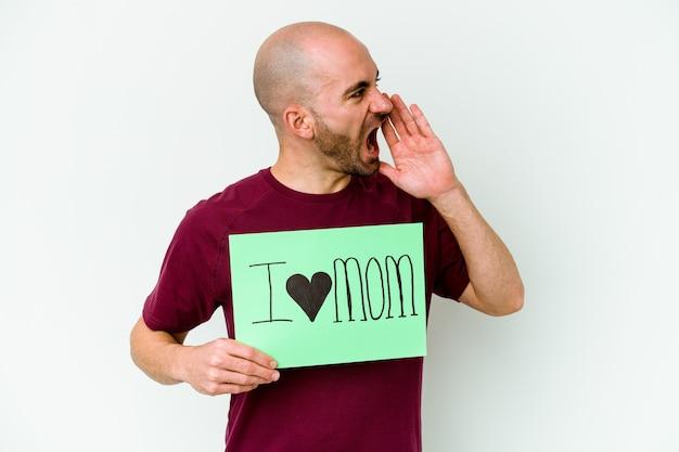 Jovem homem careca caucasiano segurando um cartaz de eu amo mãe isolado em fundo amarelo gritando e segurando a palma da mão perto da boca aberta.