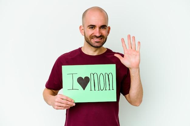 Jovem homem careca caucasiano segurando um cartaz de eu amo mãe isolado no fundo amarelo, sorrindo alegre mostrando o número cinco com os dedos.