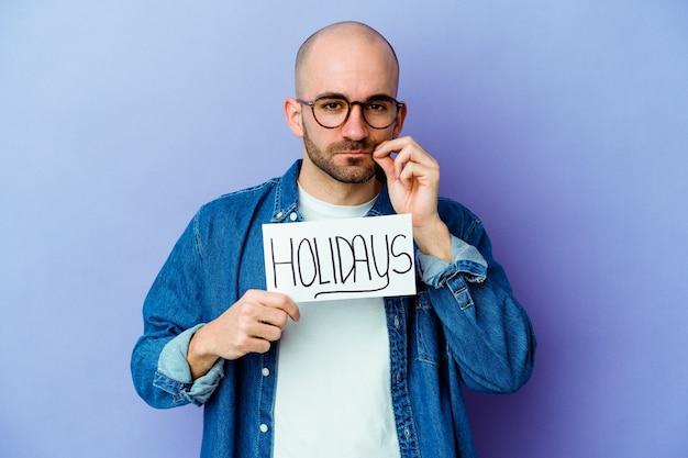 Jovem homem careca caucasiano segurando um cartaz de férias em azul com os dedos nos lábios, mantendo um segredo. Foto Premium