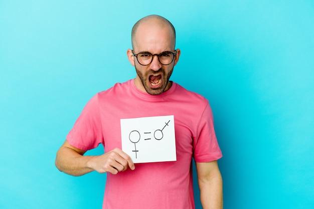 Jovem homem careca, caucasiano, segurando um cartaz de igualdade de gênero isolado na parede amarela, gritando muito zangado e agressivo