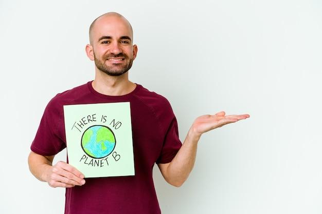 Jovem homem careca caucasiano segurando um cartaz de não há planeta b isolado no fundo roxo, mostrando um espaço de cópia na palma da mão e segurando a outra mão na cintura.