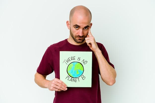 Jovem homem careca caucasiano segurando um cartaz de não há planeta b isolado no templo apontando de fundo roxo com o dedo, pensando, focado em uma tarefa.