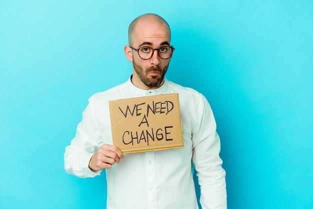 Jovem homem careca, caucasiano, segurando um cartaz de precisamos de uma mudança isolado