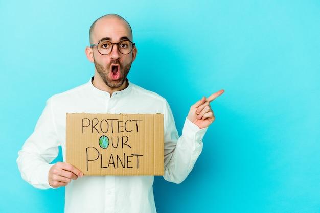 Jovem homem careca, caucasiano, segurando um cartaz de proteja nosso planeta isolado em um fundo roxo apontando para o lado
