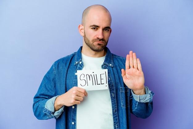 Jovem homem careca caucasiano segurando um cartaz de sorriso em pé roxo com a mão estendida, mostrando o sinal de pare, impedindo você.