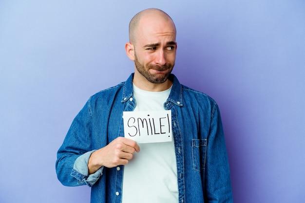 Jovem homem careca caucasiano segurando um cartaz de sorriso isolado no fundo roxo confuso, sente-se duvidoso e inseguro.