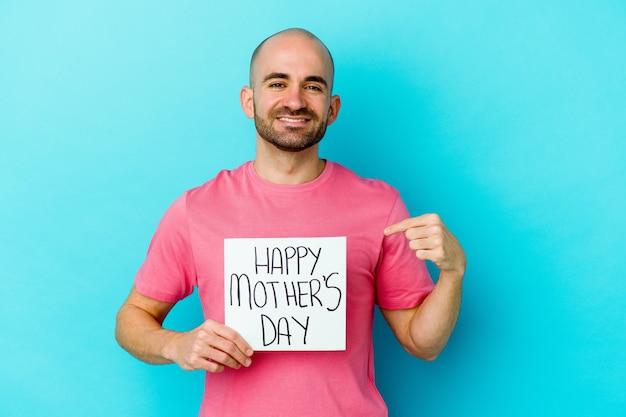 Jovem homem careca, caucasiano, segurando um cartaz do dia das mães feliz isolado na parede azul pessoa apontando com a mão para um espaço de cópia de camisa, orgulhoso e confiante