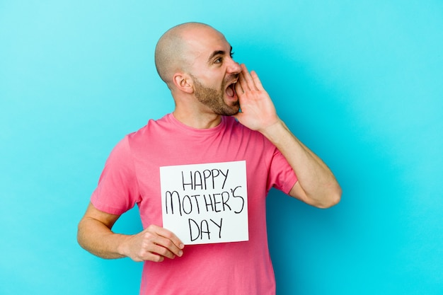 Jovem homem careca caucasiano segurando um cartaz do dia das mães feliz isolado no fundo azul, gritando e segurando a palma da mão perto da boca aberta.