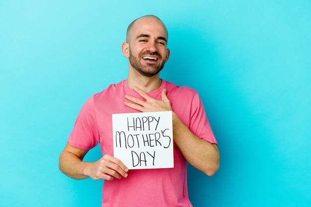 Jovem homem careca, caucasiano, segurando um cartaz do feliz dia das mães isolado