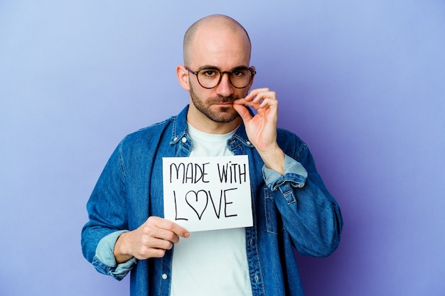Jovem homem careca caucasiano segurando um cartaz feito com amor isolado na parede roxa com os dedos nos lábios, mantendo um segredo.