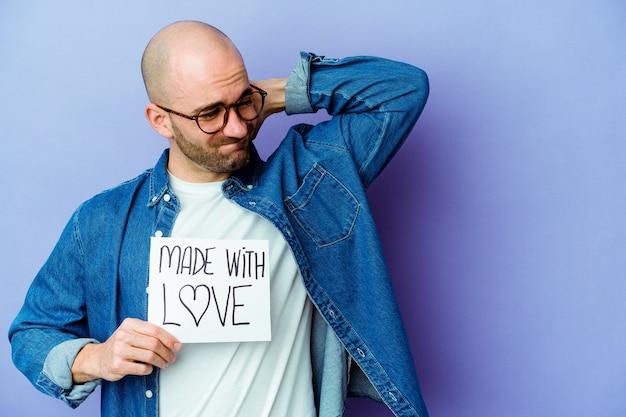 Jovem homem careca caucasiano segurando um cartaz feito com amor isolado no fundo roxo, tocando a parte de trás da cabeça, pensando e fazendo uma escolha.