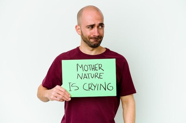 Jovem homem careca caucasiano segurando um choro da mãe natureza isolado na parede branca confuso, sente-se duvidoso e inseguro.