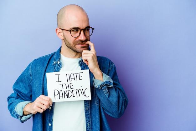 Jovem homem careca caucasiano segurando um eu odeio o cartaz de pandemia isolado na parede azul relaxado pensando em algo olhando para um espaço de cópia.