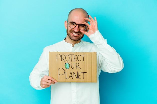Jovem homem careca caucasiano segurando um protetor nosso planeta cartaz em roxo animado, mantendo o gesto ok no olho.