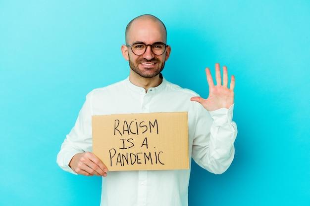 Jovem homem careca caucasiano segurando um racismo é uma pandemia isolada