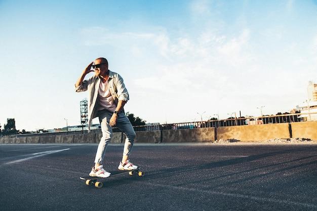 Jovem homem caucasiano andando de longboard ou skate, tiro moderno em efeito de grão de filme e estilo vintage.