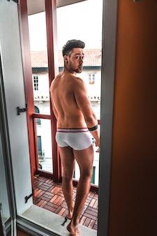 Jovem homem caucasiano apenas com boxers no terraço do apartamento