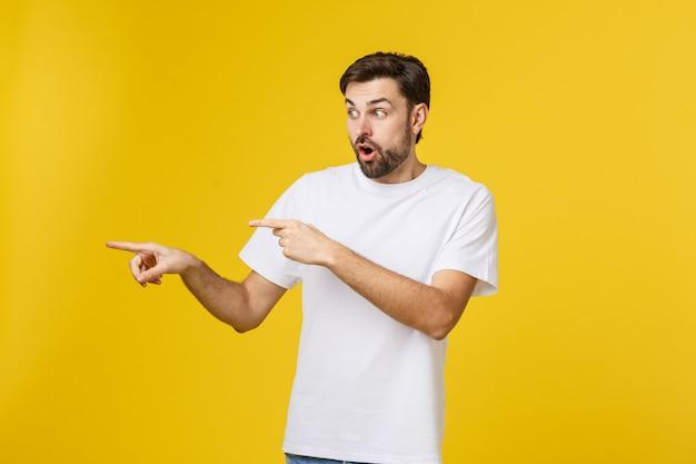 Jovem homem caucasiano apontando algo interessante em um amarelo