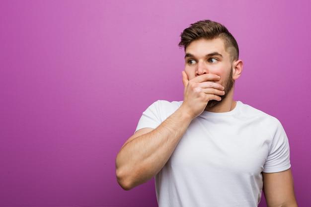 Jovem homem caucasiano bonito pensativo olhando para um espaço de cópia cobrindo a boca com a mão.