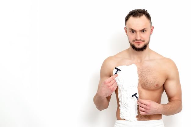 Jovem homem caucasiano com barba detém navalha raspa o peito com espuma de barbear branca. homem depilando o torso