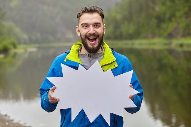 Jovem homem caucasiano com barba está segurando um pedaço de papel em branco e sorrindo, ele está na floresta e há um rio atrás dele.