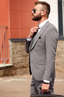 Jovem homem caucasiano com barba no terno ao lado do edifício após a reunião de negócios, cara de smoking e óculos de sol pretos ao ar livre. conceito de empresários