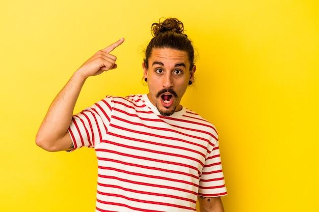 Jovem homem caucasiano com cabelo comprido, isolado em fundo amarelo, tendo uma ótima ideia, o conceito de criatividade.