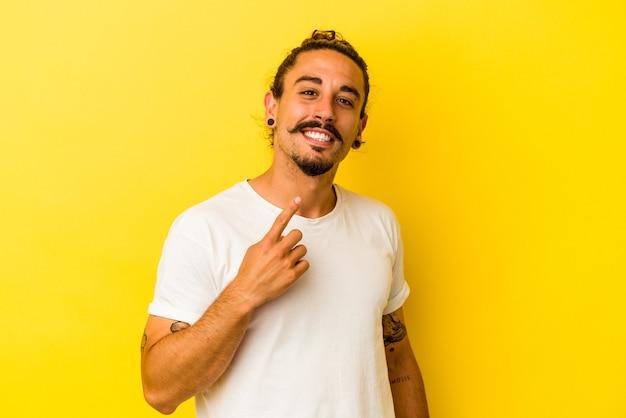 Jovem homem caucasiano com cabelo comprido, isolado em um fundo amarelo, apontando com o dedo para você como se fosse um convite para se aproximar.