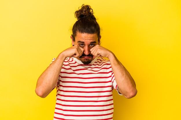 Jovem homem caucasiano com cabelo comprido, isolado em um fundo amarelo, chorando e chorando desconsoladamente.
