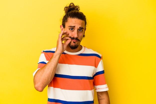 Jovem homem caucasiano com cabelo comprido, isolado em um fundo amarelo com os dedos nos lábios, mantendo um segredo.