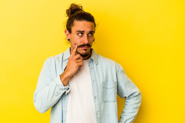 Jovem homem caucasiano com cabelo comprido, isolado em um fundo amarelo, contemplando, planejando uma estratégia, pensando na forma de um negócio.