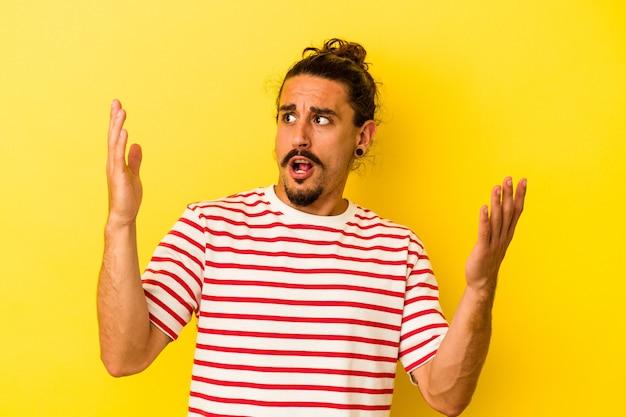 Jovem homem caucasiano com cabelo comprido, isolado em um fundo amarelo, gritando para o céu, olhando para cima, frustrado.