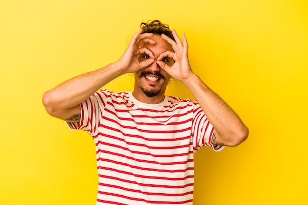 Jovem homem caucasiano com cabelo comprido isolado em um fundo amarelo, mostrando sinal de aprovação sobre os olhos