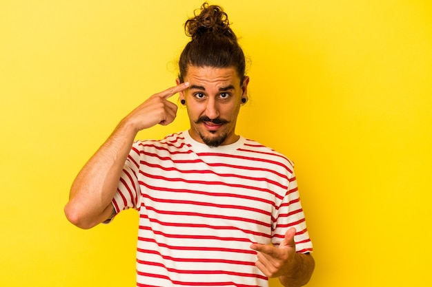 Jovem homem caucasiano com cabelo comprido, isolado em um fundo amarelo, mostrando um gesto de decepção com o dedo indicador.
